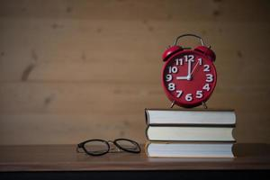 Despertador a las 9 de la mañana en la pila de libros con gafas en la mesa de madera