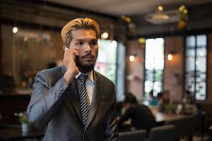 Apuesto hombre de negocios hablando por teléfono mientras se toma un descanso en el café