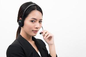Joven mujer asiática con auriculares de teléfono de apoyo, aislado sobre fondo blanco. foto