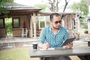 El empresario trabaja en tableta y escribiendo mientras está sentado en la mesa de madera en casa