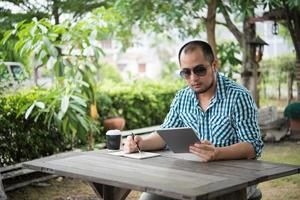 El empresario trabaja en tableta y escribiendo mientras está sentado en la mesa de madera en casa foto