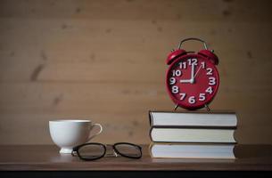 Despertador a las 9 de la mañana en una pila de libros con vasos y una taza de café en la mesa de madera