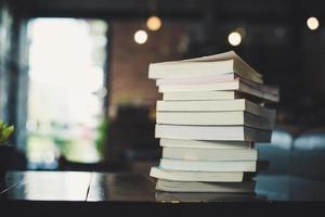 Piles of books on table over blurred library background
