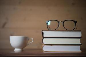 Vasos en una pila de libros y una taza de café en la mesa de madera