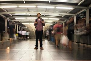 Apuesto hombre barbudo con mochila de pie en la calle viajando de noche foto