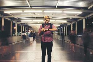 Guapo hombre barbudo de pie en la calle mientras mira SmartWatch viajando de noche foto