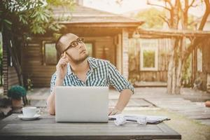 Young businessman with glasses working at workplace, feeling stressed, looking at laptop photo