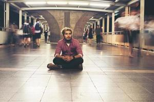 Hipster bearded man sitting on the floor while traveling at night photo
