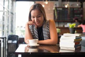 Asian woman relaxing and reading a book in the cafe