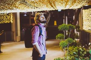 Apuesto hombre barbudo con mochila de pie en la calle mientras viaja de noche foto