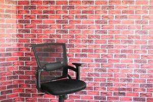 Silla vacía negra contra una pared interior foto
