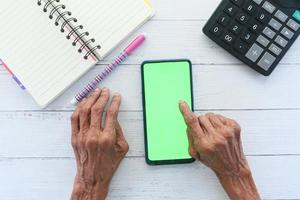 Anciana usando un teléfono inteligente en un escritorio foto