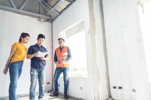 Young Asian engineers building a house