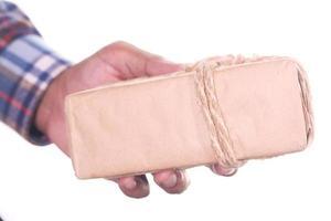 La mano del hombre sosteniendo una caja de regalo aislado en blanco fundamento