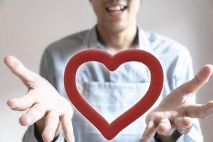 Man's hand holding a heart