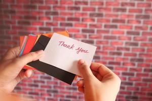 mujer sosteniendo una tarjeta de agradecimiento