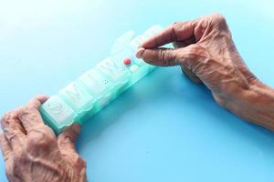 Vista superior de manos mayores tomando medicamentos de un pastillero foto