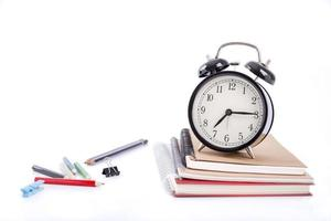 A pile of books with colored pen and alarm clock on white background