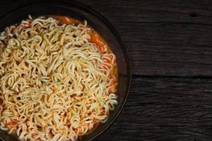 Instant noodles in a bowl on wooden background photo