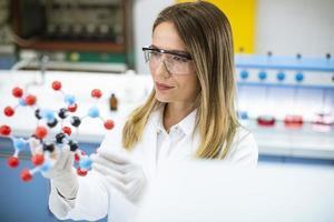 Química femenina mantenga modelo molecular en el laboratorio. foto