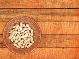 Peanuts in wicker basket on orange wooden table background photo