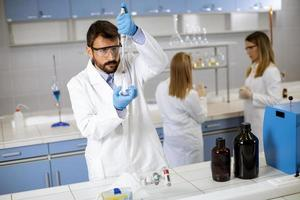 Young researcher in protective workwear standing in the laboratory and analyzing flask with liquid photo