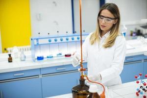 Investigadora en ropa de trabajo protectora de pie en el laboratorio y analizando matraz con muestra líquida foto