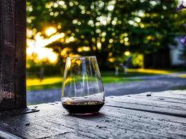 Copa de vino retroiluminado en un porche con árboles y patio en el fondo al atardecer