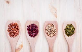 Beans and lentils in wooden spoons on a wooden background photo