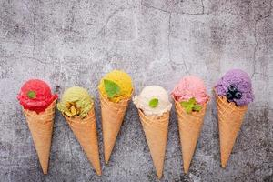 Colorful ice cream in cones on concrete background