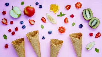 Waffle cones and fruit on a purple background