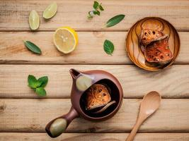 Tea pot with fresh herbs on a wood table photo