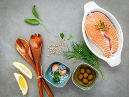 Raw salmon fillet in a white bowl with ingredients