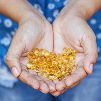 pastillas de aceite de pescado en las manos foto
