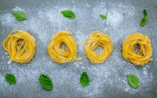 Fresh pasta and basil on a gray background