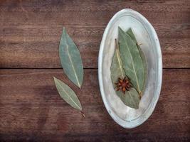 hojas de laurel en un cuenco de cerámica sobre una mesa foto