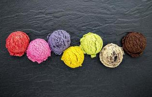 Colorful scoops of ice cream on slate photo