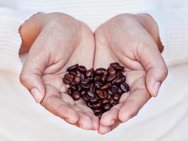 granos de cafe en las manos foto
