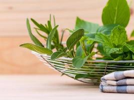 Bowl of fresh herbs on a table photo