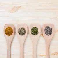 Dried spices in wooden spoons on a wood background photo