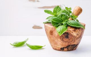 Herbs in a wooden mortar on shabby white photo