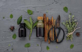 Bottle of essential oil with fresh herbs and pruning scissors photo