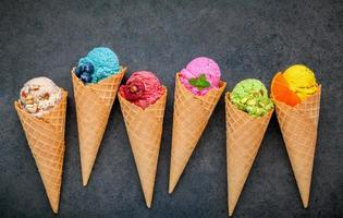 Colorful ice cream in waffle cones on a dark gray background