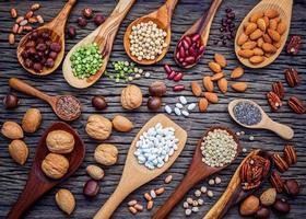 Legumes and nuts in spoon on a dark wood background photo