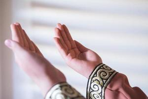 Hands of a Muslim or Islamic woman gesturing while praying at home photo