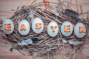 huevos de pascua con plumas y elementos de nido foto