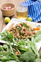 Hot and spicy grilled pork salad on white plate on wooden table