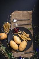 Patatas, patatas fritas y cerezas en placa negra con utensilios de arpillera y mesa de madera oscura. foto