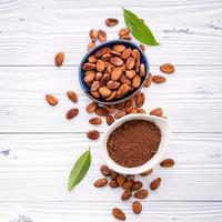 Top view of cocoa powder and cacao beans on a white wooden background
