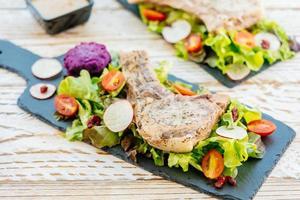 Filete de carne de chuleta de cerdo a la parrilla a la parrilla sobre placa negra con verduras